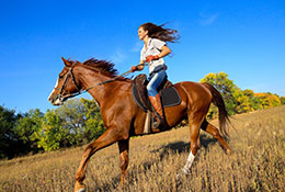 Majestic-woman-riding-horse-with-wind-blowing-through-hair
