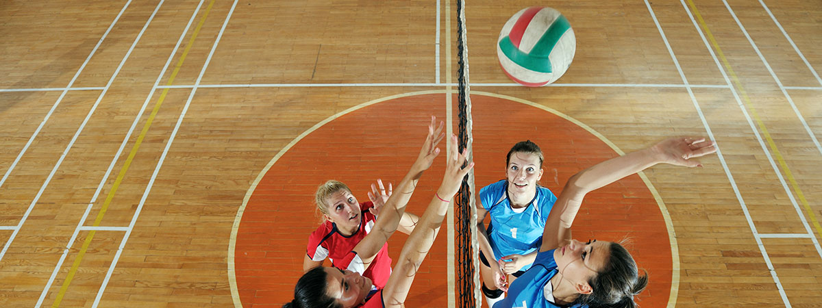 women-playing-volleyball-wood-floor