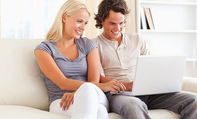 couple-sitting-on-couch-with-computer
