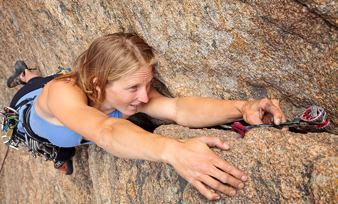 woman climbing rock crack