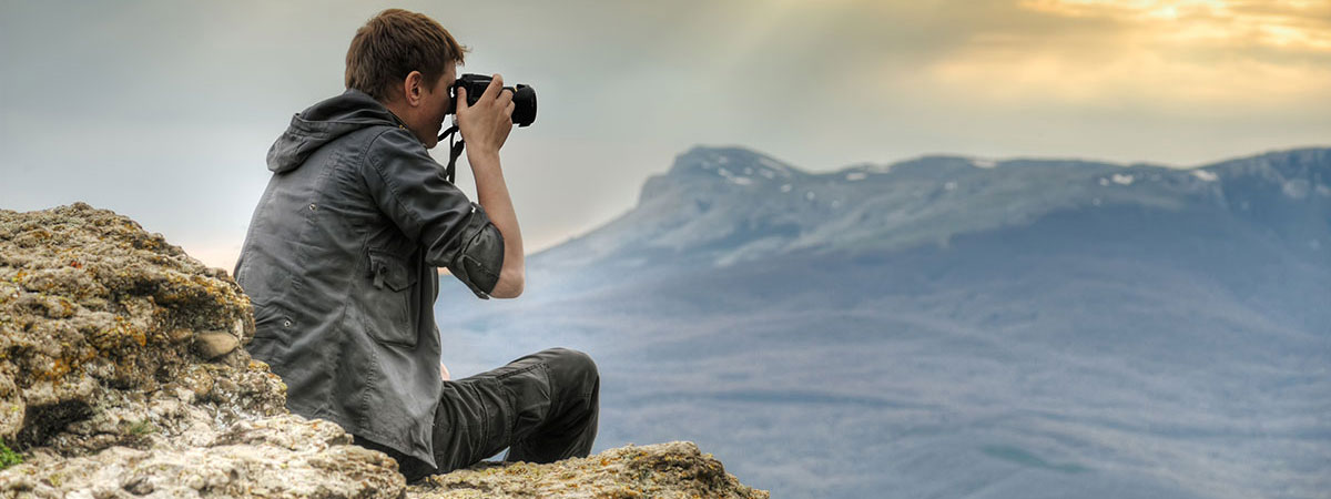 man-on-mountain-with-camera